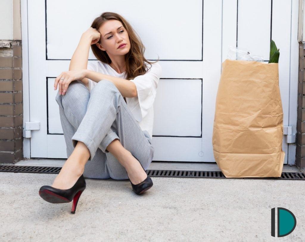 Deprimierte Frau, die ihren Schlüssel verloren hat und nun vor ihrer Haustür sitzt, da sie ausgesperrt ist.